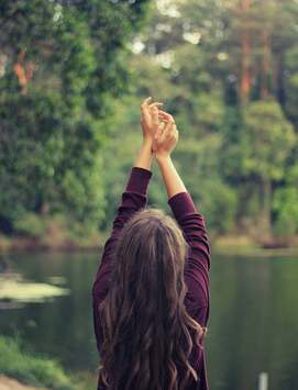 Picture of girl with hands raised to sky